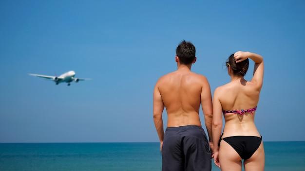 Petite amie en bikini et petit ami se tiennent près de l'immense océan calme et regardent l'avion approcher sous le ciel bleu vue arrière