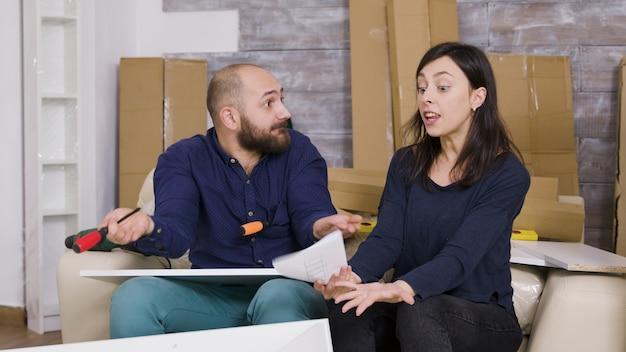 Petite amie en colère frappant son petit ami avec des instructions sur les meubles. couple assemblant des meubles dans un nouvel appartement.