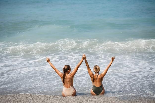La petite amie de deux filles est assise sur le rivage sablonneux de la mer et les vagues les ont trempées dans des maillots de bain par une chaude journée ensoleillée