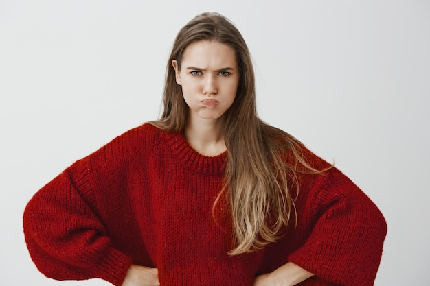 Petite amie enfantine veut de l'attention. portrait de femme européenne offensée mécontent en pull rouge lâche, se tenant la main sur les hanches, bouder et froncer les sourcils, se disputer et être insulté