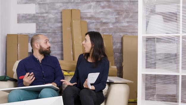 Petite amie frappant son petit ami avec des instructions tout en assemblant des meubles dans leur nouvel appartement.