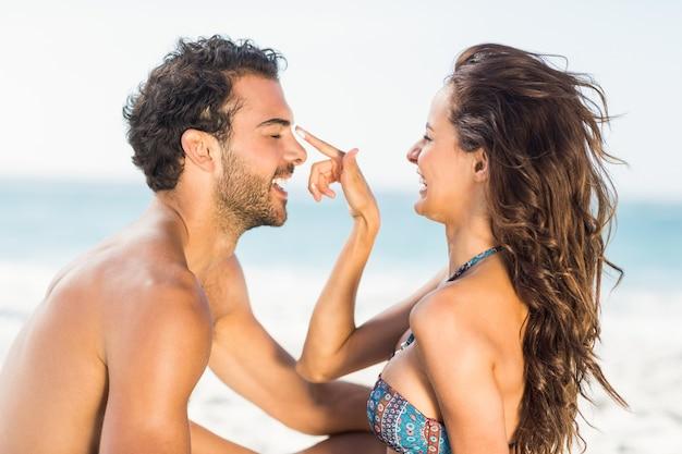 Petite amie heureuse, mettre de la crème solaire sur son petit ami
