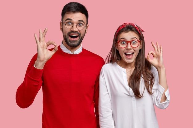Petite amie et petit ami caucasiens positifs charismatiques font un geste correct, dites ne vous inquiétez pas, affirmez que tout est sous contrôle, posez sûr de vous