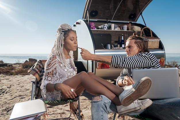 Petite amie qui fume. homme aux cheveux blonds donnant un briquet à sa petite amie qui fume une cigarette assis près de la remorque d'accueil