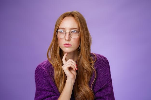 Petite amie résolvant un casse-tête comme un détective faisant des hypothèses en se concentrant sur un problème de strabisme en regardant à gauche déterminé et réfléchi portant des lunettes touchant la mâchoire tout en pensant sur un fond violet.