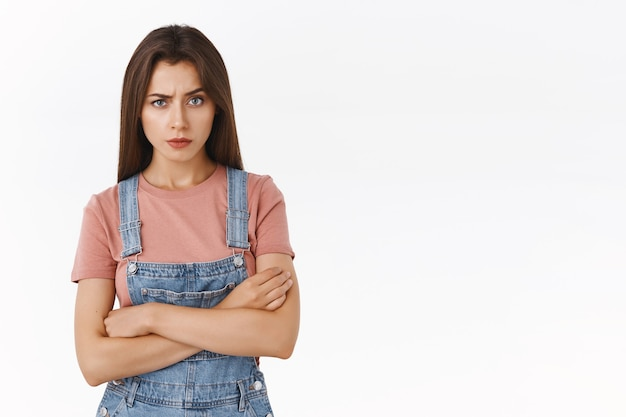 Une petite amie sérieuse, autoritaire et sceptique, agacée, demande des explications en regardant la caméra en colère et en colère, les mains croisées sur la poitrine, debout sur fond blanc concentré