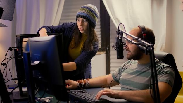 Petite amie soutient son petit ami joueur professionnel, jouant à un jeu vidéo en ligne à l'aide d'un équipement professionnel de streaming