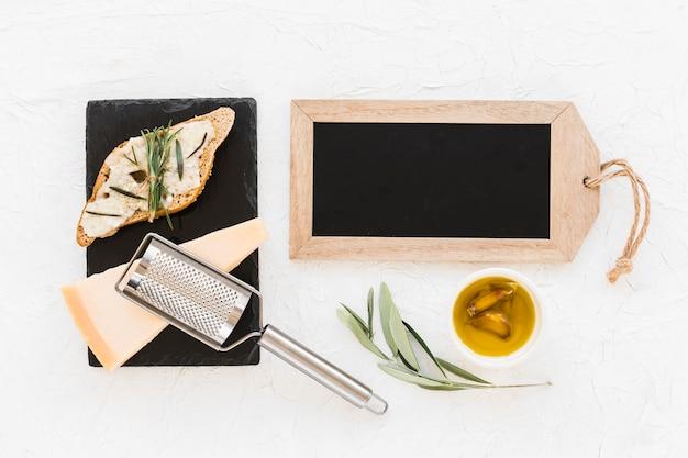 Petite ardoise en bois avec pain, fromage et huile sur fond blanc