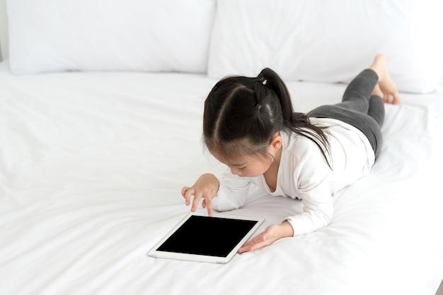 Petite asiat aime regarder dessin animé sur une tablette intelligente dans la chambre