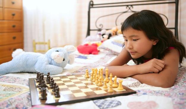 Petite asiat jouant aux échecs avec un lapin en peluche