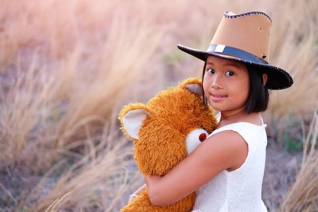 Petite asiat joue dans le champ de la prairie et câlin ours en peluche marron et a un visage lumineux et
