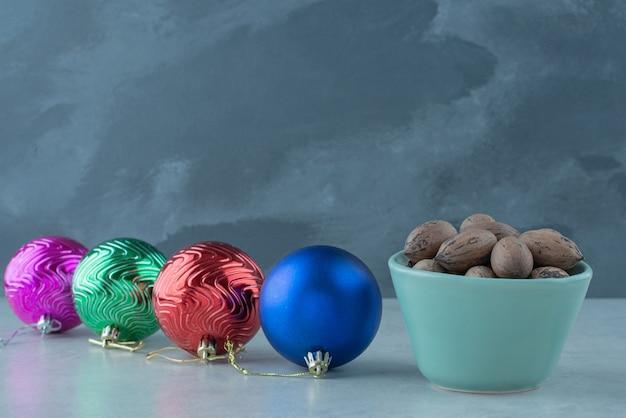 Une petite assiette bleue pleine de noix avec des boules de noël sur fond de marbre. photo de haute qualité