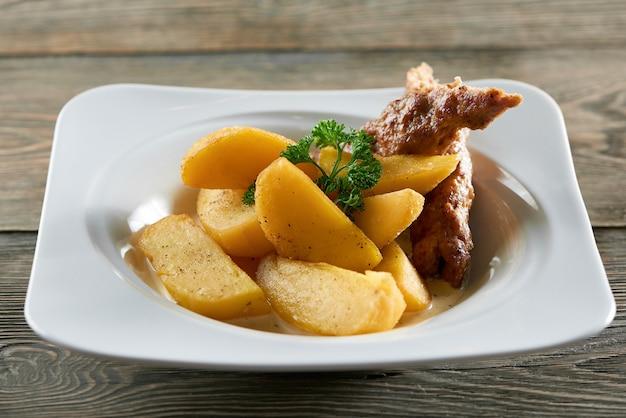 Petite assiette de restaurant blanche servie avec des tranches de pommes de terre frites dorées, une saucisse fine et décorée de feuilles de persil. semble très délicieux et nourrissant.