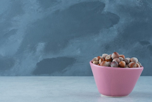 Une petite assiette rose pleine de noix sur fond de marbre. photo de haute qualité