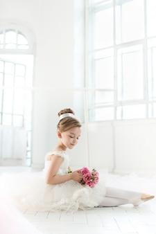 Petite balerine en tutu blanc en classe à l'école de ballet