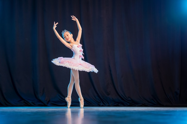 Une petite ballerine danse sur scène dans un tutu blanc sur des pointes, une variation classique.
