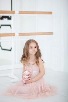 Une petite ballerine en robe est assise dans un cours de danse par terre. petite fille tenant un carrousel de jouet musical. l'enfant reçoit un cadeau. jouet de carrousel musical vintage. salle de classe salle de ballet à l'intérieur