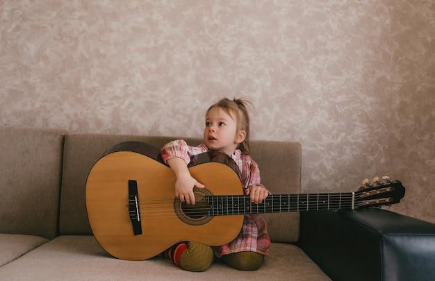Petite belle fille apprend à jouer de la guitare assis à la maison sur le canapé