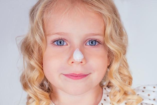 Petite et belle fille blonde aux cheveux bouclés en robe mignonne éponger la crème solaire sur le visage. yeux bleus, peau parfaite, sur le nez crème spf portrait en gros plan sur fond blanc en studio.