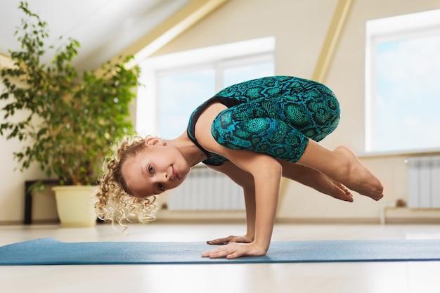 Petite belle fille blonde pratiquant le yoga en studio faisant l'exercice de poirier kakasana ou corbeau pose sur un tapis de gymnastique