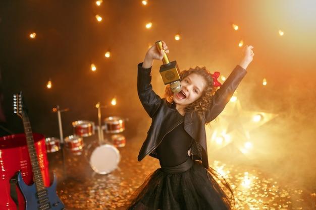 Petite belle fille chantant en studio d'enregistrement
