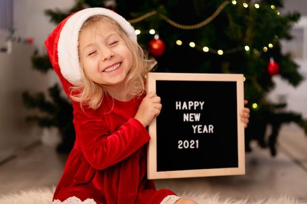 Petite belle fille avec un chapeau de père noël et une robe de noël rouge est allongée sous le sapin de noël et en riant, à côté d'un tableau noir et du texte de lettres blanches bonne année 2021. photo de haute qualité