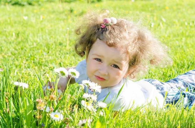 Petite belle fille dans le champ avec des marguerites. enfant gai avec des fleurs dans la nature.