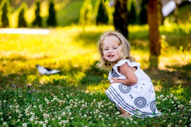 Petite belle fille dans le parc dans une robe blanche