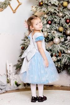 La petite belle fille dans une robe futée se tient près de l'arbre de noël