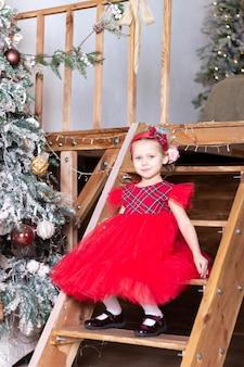 La petite belle fille dans une robe rouge se repose sur les escaliers près de l'arbre de noël