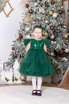 La petite belle fille dans une robe verte se tient près de l'arbre de noël