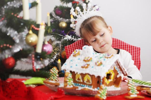 La petite belle fille décore la maison de pain d'épice de glaçage
