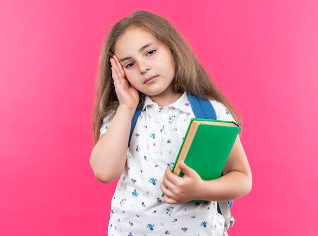 Petite belle fille dérangée aux cheveux longs avec un sac à dos tenant un cahier regardant devant lui toucher la tête debout sur un mur rose