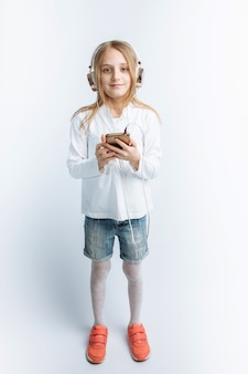 Petite belle fille, écouter de la musique et regarder le téléphone
