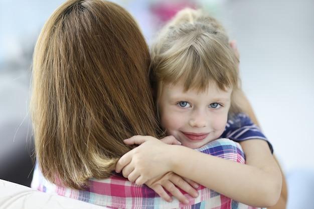 Petite belle fille embrasse sa mère et portrait souriant