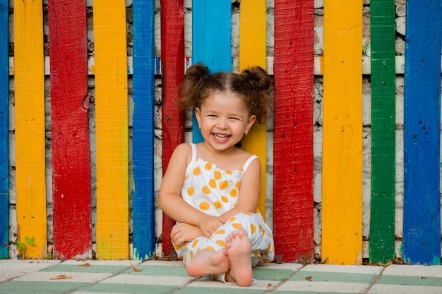 Une petite belle fille est assise près d'une clôture en bois multicolore