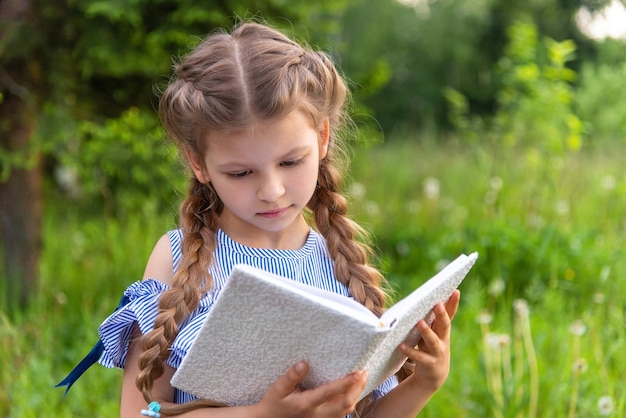 Petite belle fille lisant un livre dans la forêt.