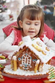 Petite belle fille avec une maison de pâte de pain d'épice