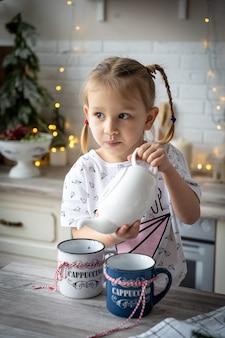 Petite belle fille en pyjama verse du thé d'une théière sur une tasse à la table de la cuisine