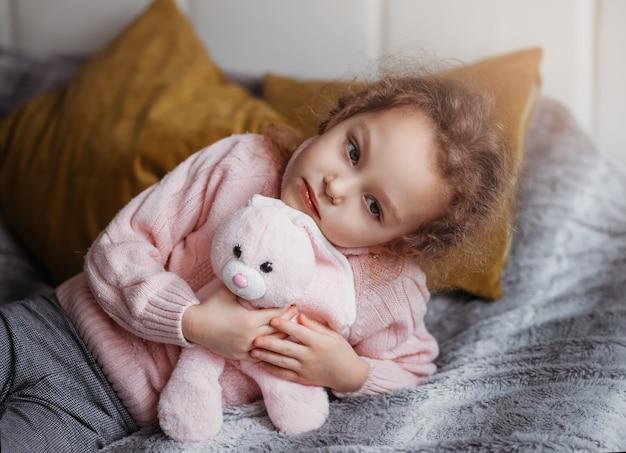 Petite belle fille se trouve sur le lit avec une peluche et triste