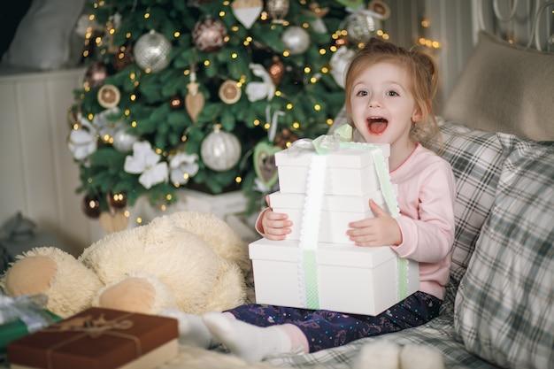 Petite belle fille avec ses cadeaux est assise dans son lit