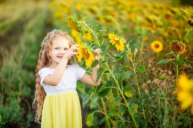 Une petite belle fille tient un tournesol dans un champ en été