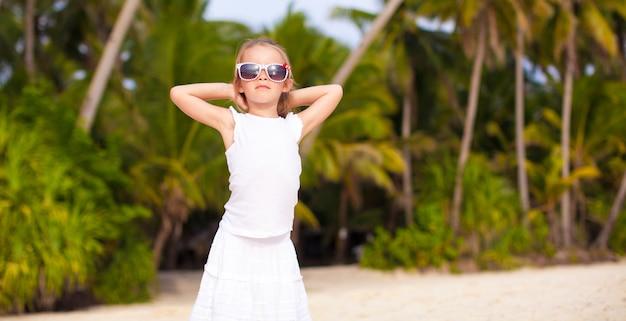 Petite belle fille vêtue d'une robe longue sur une plage tropicale