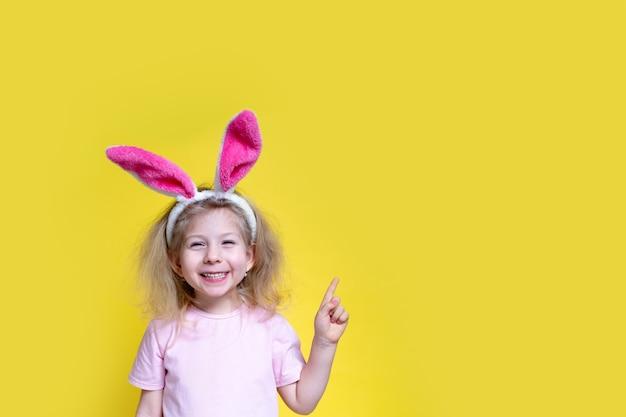 Petite blonde heureuse avec des oreilles de lapin de pâques sourit et tient son doigt sur un fond jaune pointant vers l'espace de copie, le concept de la fête religieuse de pâques.