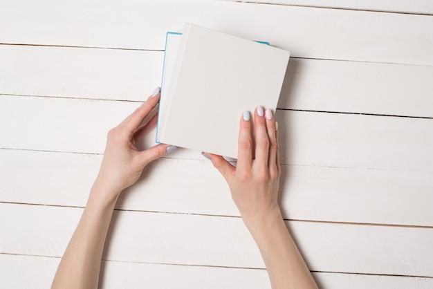 Petite boîte blanche semi-ouverte entre des mains féminines. vue de dessus. table blanche sur le