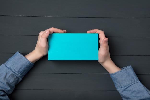 Petite boîte bleue dans les mains des enfants. surface noire. enfant tenant une boîte-cadeau. vue de dessus.