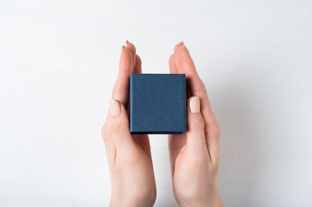 Petite boîte bleue dans les mains féminines.