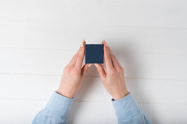 Petite boîte bleue en mains féminines