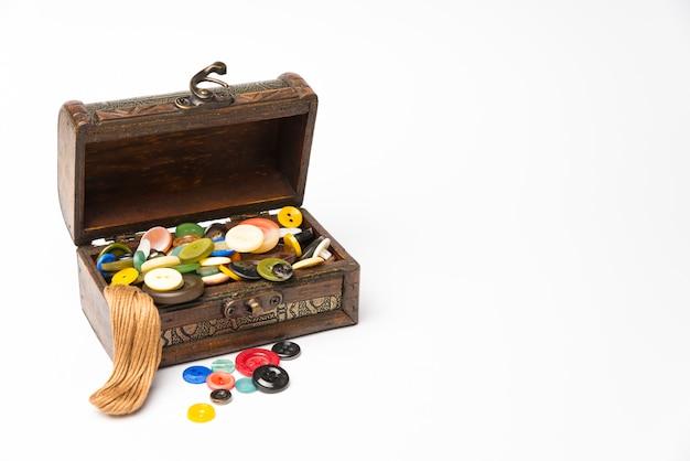 Petite boîte en bois avec des boutons et des fils sur un fond blanc