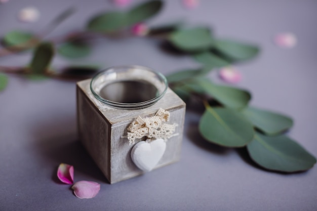 Petite boîte en bois pour bougies avant branche verte sur table